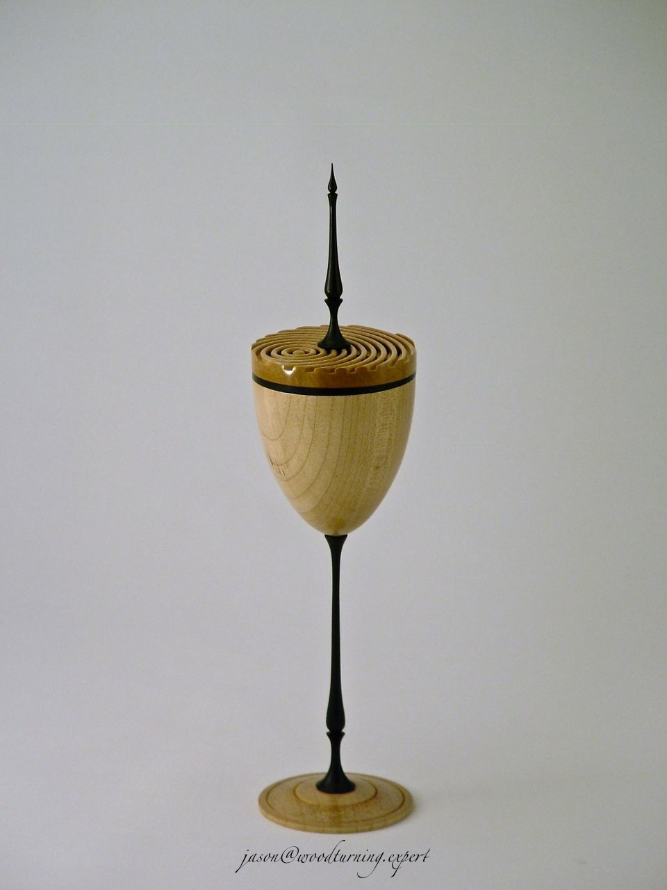 A Woodturned goblet in Sycamore and Ebony with a fine stem and finial, and a multi-center Holtzapffel style lid